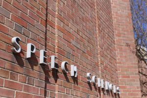 """Photo of a brick building with a sign that says """"speech sciences"""""""